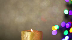 Candle with christmas tree lights in background Stock Footage
