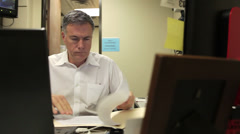 Businessman working on paperwork in his office Stock Footage