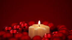 Christmas candle turning in red ornaments Stock Footage