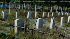 Small town cemetery military graves with barbed wire rack focus Stock Footage