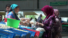 Veiled women at Central Asian bazaar, colorful dresses, Islam, muslim, food Stock Footage