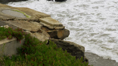 Re-bar sticking out of broken concrete above waves Stock Footage