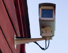 Enclosed professional security system video camera mounted outside home prote Stock Photos