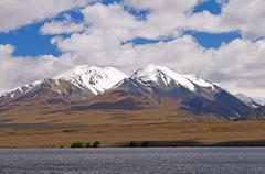 snowy peaks above an alpine plain - stock photo