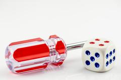 screwdriver and dice on the white background - stock photo
