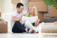 Couple sitting on floor looking at house plans Stock Photos