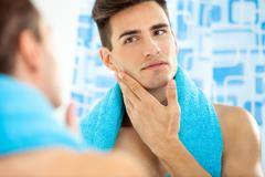 man touching his face after shaving - stock photo