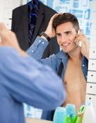 man looks himself at mirror while preparing for job - stock photo