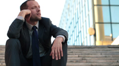 Bored young businessman sitting on stairs in the city HD Stock Footage