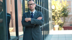 Portrait of serious young businessman stand by office building HD Stock Footage