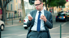 Businessman with smartphone eating sandwich by city street HD Stock Footage
