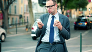 Stock Video Footage of Businessman with smartphone eating sandwich by city street HD