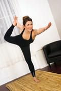 young attractive woman balances standing pose yoga practice dance studio - stock photo