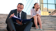 Young business people with cellphone and documents in the city HD Stock Footage