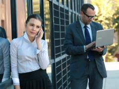 Young business people with laptop and cellphone by the building NTSC Stock Footage