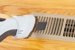 Cleaning heater vent withvacuum Stock Photos