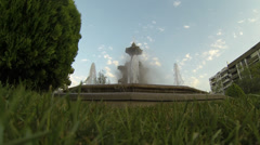Large fountain sprays water with blue sky in the background and grass in fore Stock Footage