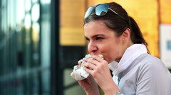 Young businesswoman eating sandwich in the city HD - stock footage