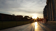 Backlight at sunset by people walking in Piazza dei Miracoli, Pisa. Stock Footage