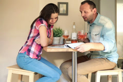 Couple in home, chatting over magazine NTSC Stock Footage