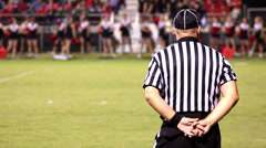 Referee onlooking from sideline at football game Stock Footage