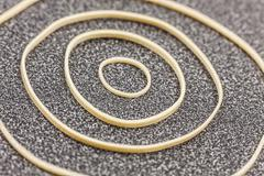 Different size rubber bands form a circular design on office desktop Stock Photos