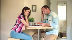 Sad, overwhelmed couple counting bills in home HD Stock Footage