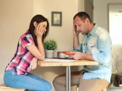 Sad, overwhelmed couple counting bills in home NTSC - stock footage