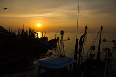 fishing boats anchored in the sea, floating peacefully in the evening. - stock photo