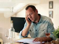 Unhappy, sad man with bills talking on cellphone in home NTSC Stock Footage