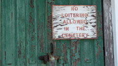 Locked door with no loitering sign in cemetery Stock Footage