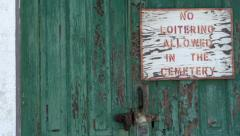 Old door with no loitering sign pan shot Stock Footage