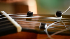 Luthier placing the chord of a guitar, close up Stock Footage