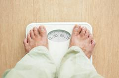 Man standing on weight scales with bare foot Stock Photos