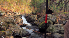 Lone young male reaches a stunning waterfall on his hiking adventure Stock Footage