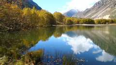 A beautiful lake with yellow trees on the beach and snow-capped peaks Stock Footage