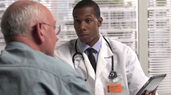 Doctor holding a tablet talking to patient Stock Footage