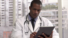 Doctor using touchscreen tablet Stock Footage