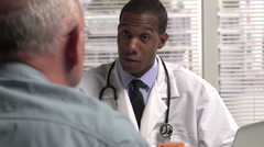 Male doctor talking with patient - stock footage