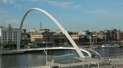 People walk over gateshead millennium bridge, newcastle on tyne, england Stock Footage