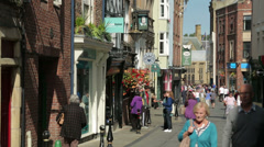 Shoppers walk along saddler street in durham city centre, england Stock Footage