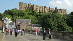 People cross bridge with castle behind, durham, england Stock Footage
