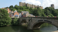 People cross bridge with castle behind, durham, england Stock Footage