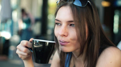 Beautiful young woman drinking cappuccino in cafe HD Stock Footage