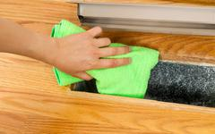 Cleaning inside heater floor vent with microfiber rag Stock Photos