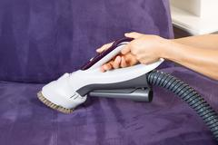 Cleaning leather sofa with vacuum brush Stock Photos