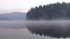 Early morning sunrise and drifting fog through the trees over the mountain lake Stock Footage