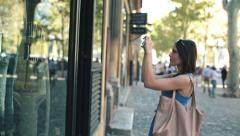 Woman taking photo of clothes on shop window in the city HD Stock Footage