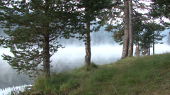 Early morning sunrise and drifting fog through the trees over the mountain lake - stock footage