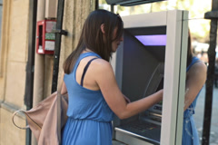 Young woman taking cash from ATM machine in the city NTSC - stock footage